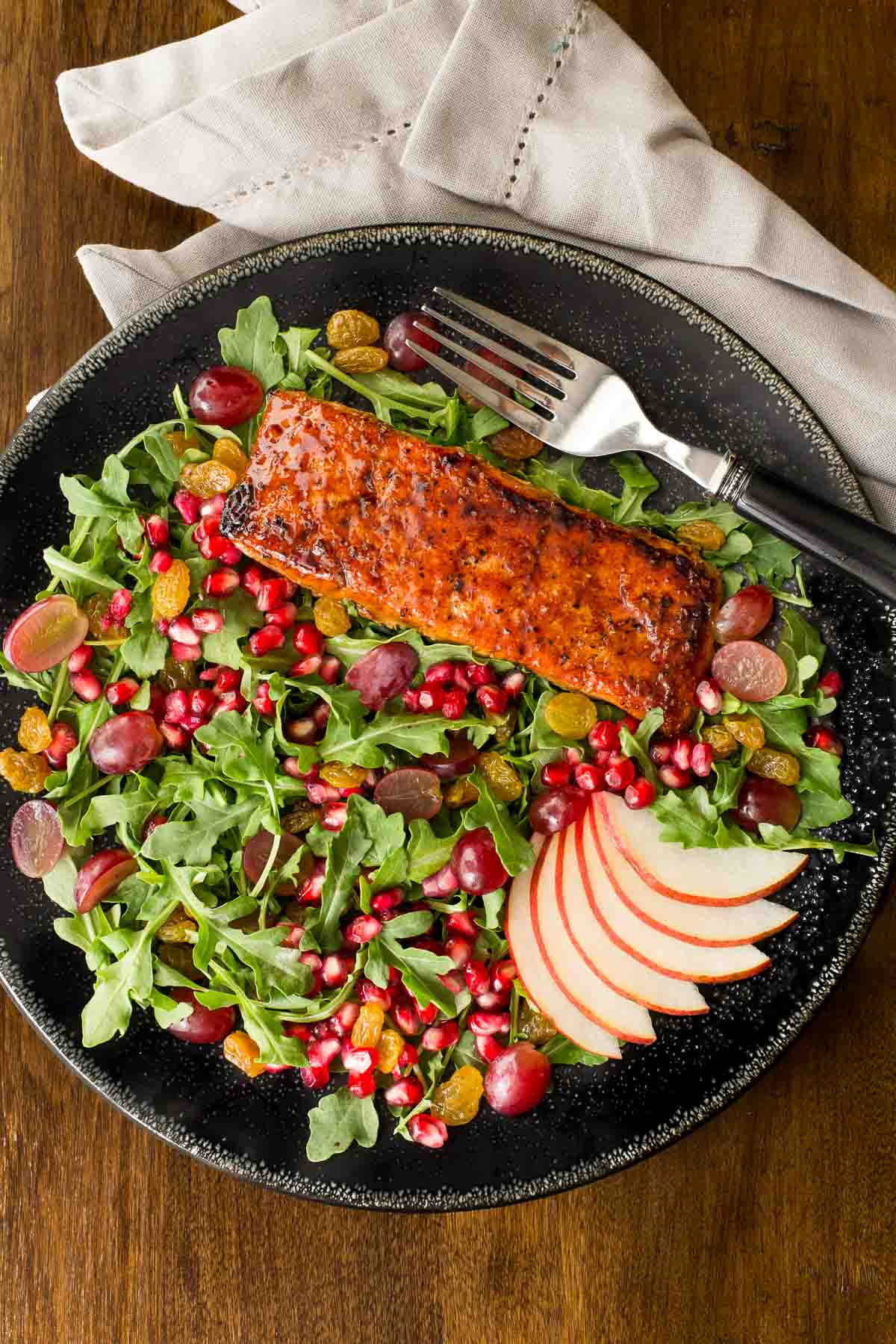 Overhead picture of Asian Glazed Salmon Salad on a black plate and a wooden table