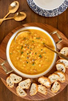 Overhead vertical photo of Golden Split Pea Soup in a pot surrounded by toasted crostini.