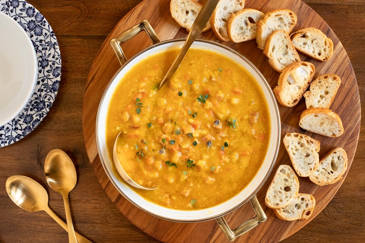 Overhead horizontal photo of a pot of Golden Split Pea Soup surrounded by toasted crostini.