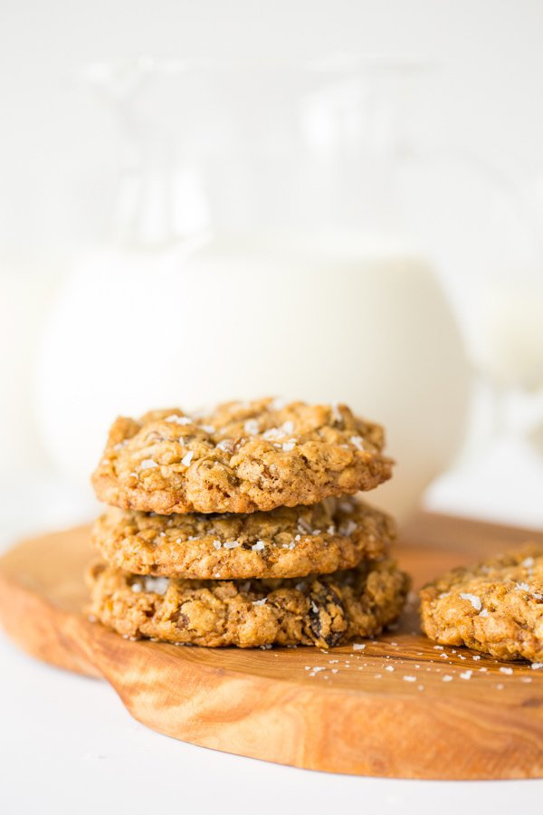 Vertical photo a stack of Grannie Annie's Oatmeal Raisin Cookies with pitcher of milk in the background.