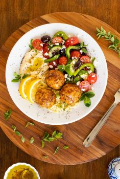 Overhead vertical photo of a serving bowl with Greek Chicken Meatballs on a bed of orzo with a Greek veggie salad.