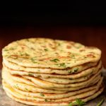 Vertical picture of Greek Yogurt Turkish Flatbread (Bazlama) stacked on a cutting board