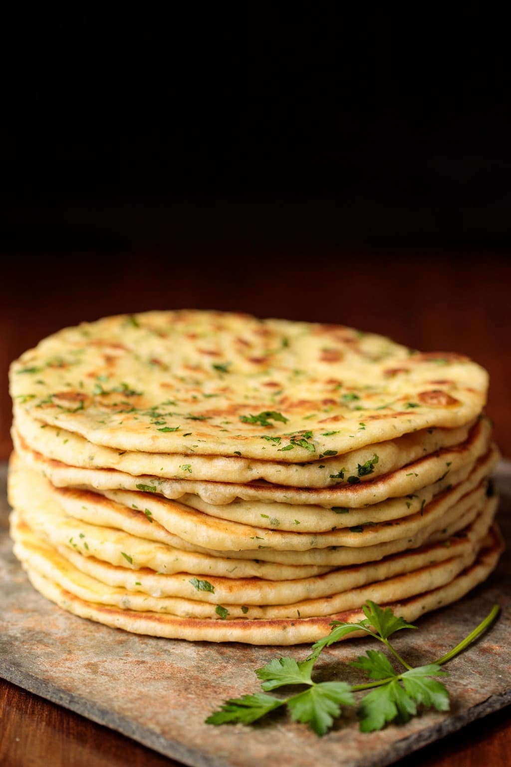 Vertical photo of Greek Yogurt Turkish Flatbread (Bazlama) stacked on a slate cutting board.
