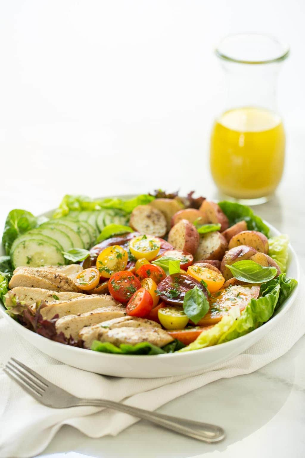 Vertical image of Grilled Chicken with Tomato Cucumber Salad.