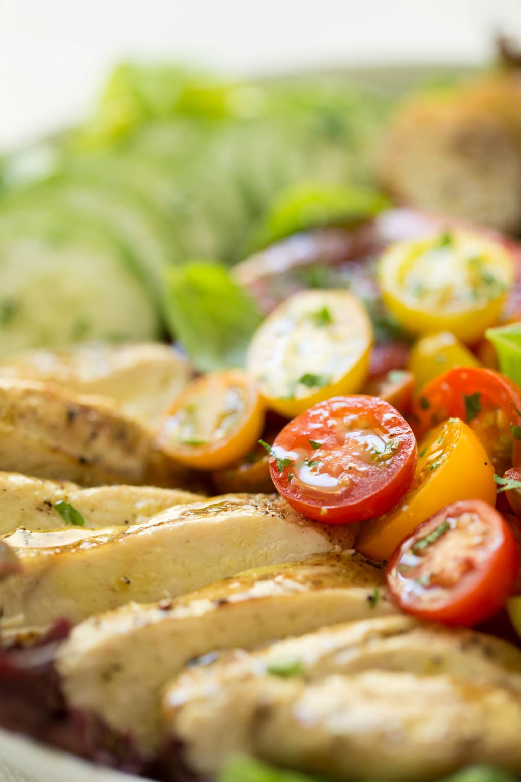 A horizontal photo of a Grilled Chicken Tomato Cucumber Salad featuring the chicken and heirloom cherry tomatoes.