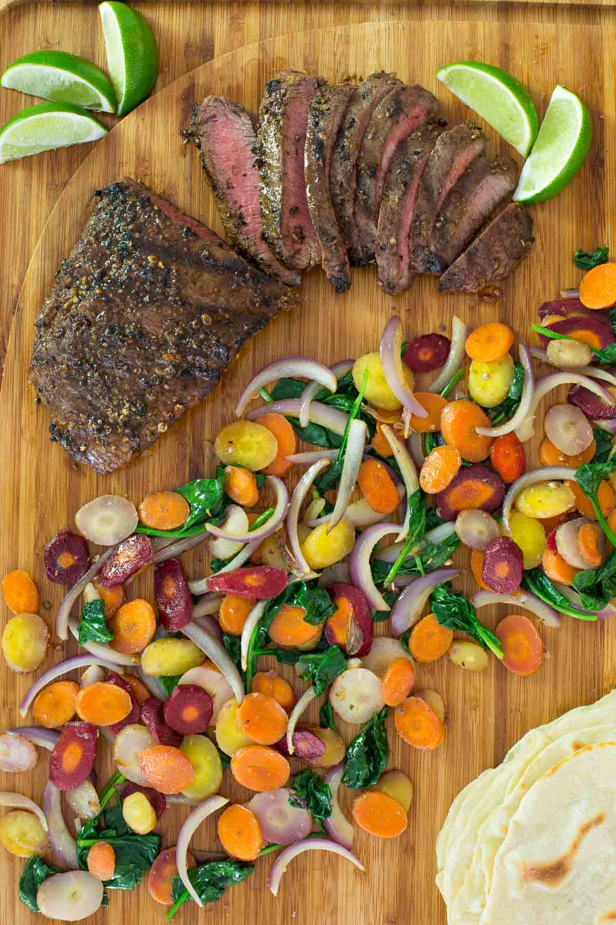 Overhead photo of Grilled Mexican Flat Iron Steak with Rainbow Carrots on a bamboo wood cutting board.