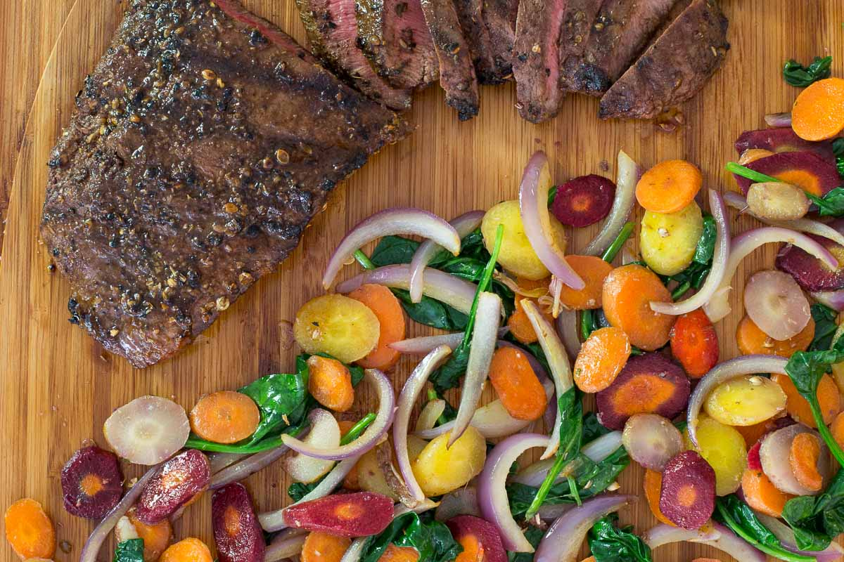 Overhead closeup photo of a Grilled Mexican Skirt Steak with Rainbow Carrots along side on a bamboo cutting board.