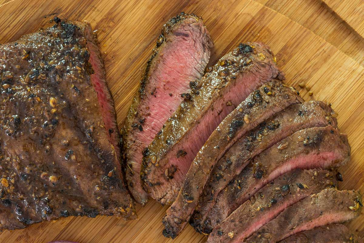 Closeup overhead photo of a Grilled Mexican Flat Iron Steak on a bamboo cutting board.