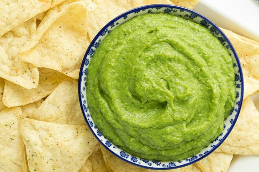 Overhead photo of a bowl of Guasacaca (Venezuelan Guacamole) surrounded by tortilla chips.
