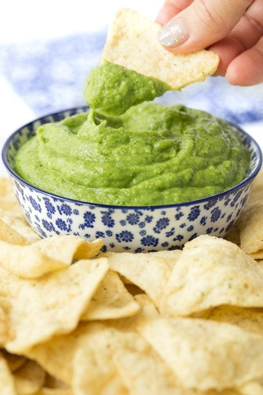 Vertical picture of Guasacaca (Venezuelan Guacamole ) in a blue and white bowl with chips