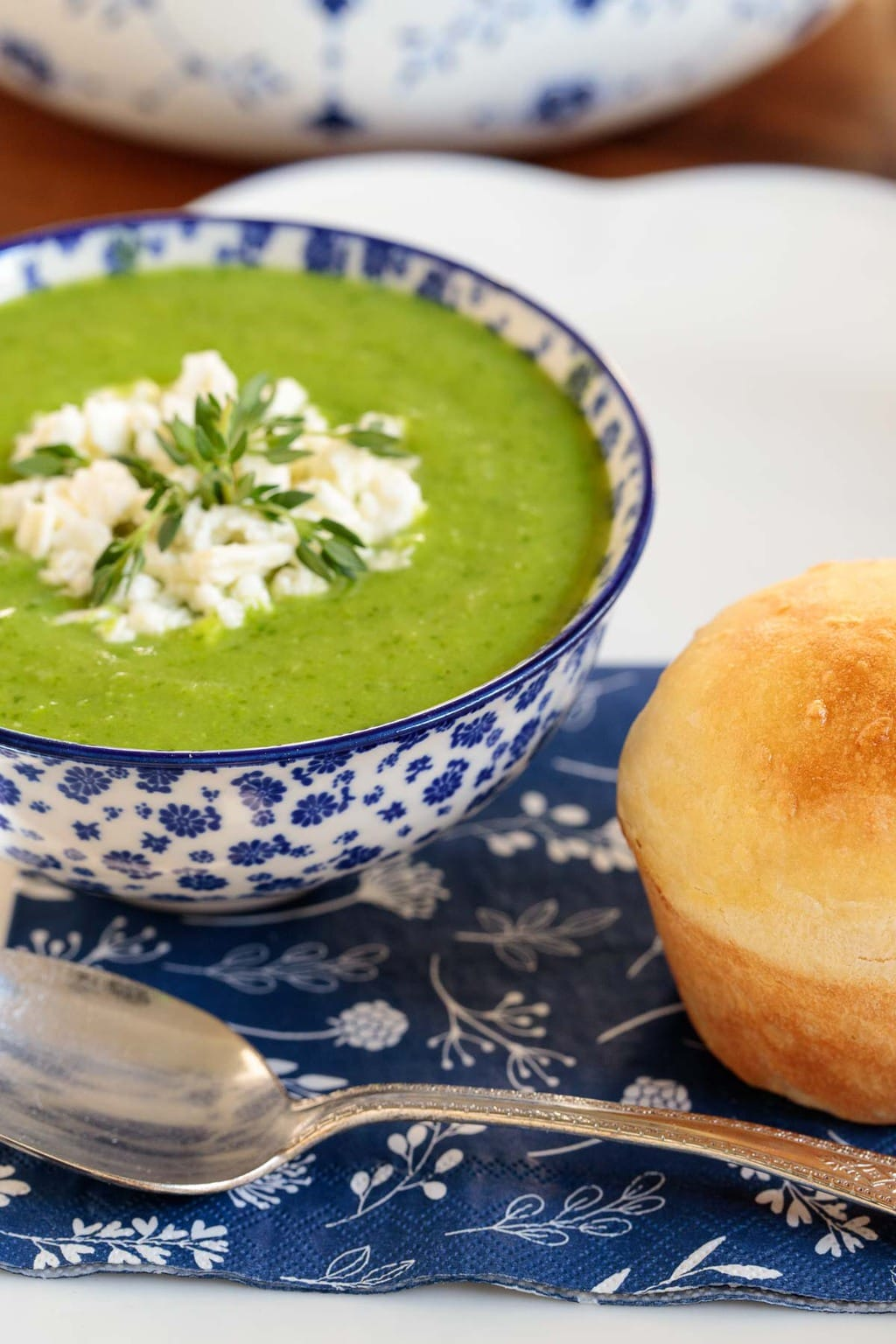 Closeup photo of a serving of Ham and Fresh Pea Soup in a blue and white patterned soup bowl next to a homemade brioche roll.