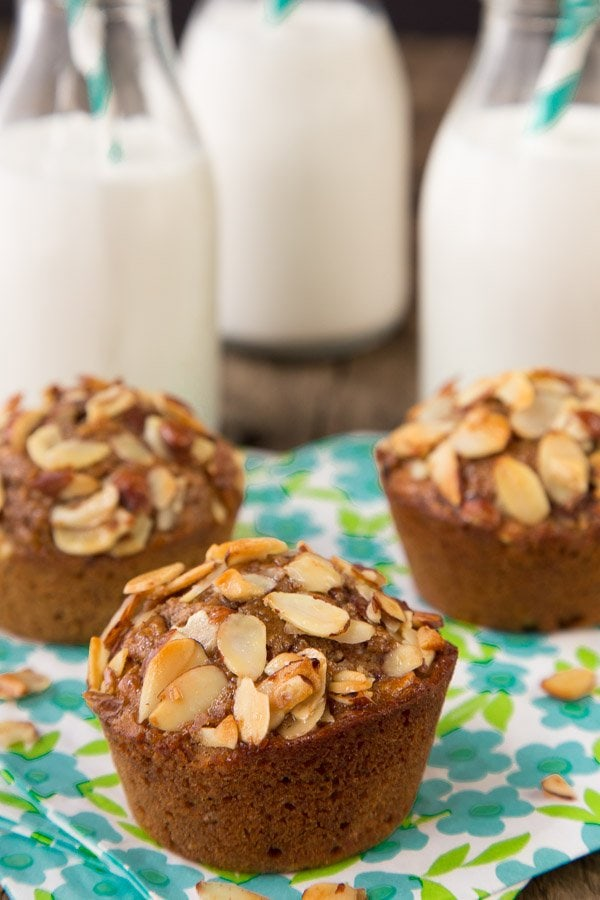 Photo of three Healthy Banana Bran Muffins on turquoise and green napkins with small bottles of milk in the background.
