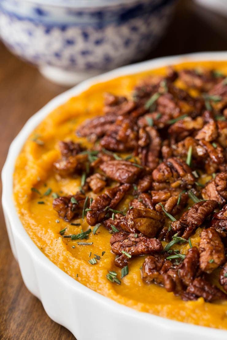 Close up vertical picture of a Healthy Butternut Sweet Potato Casserole topped with pecans in a white dish.