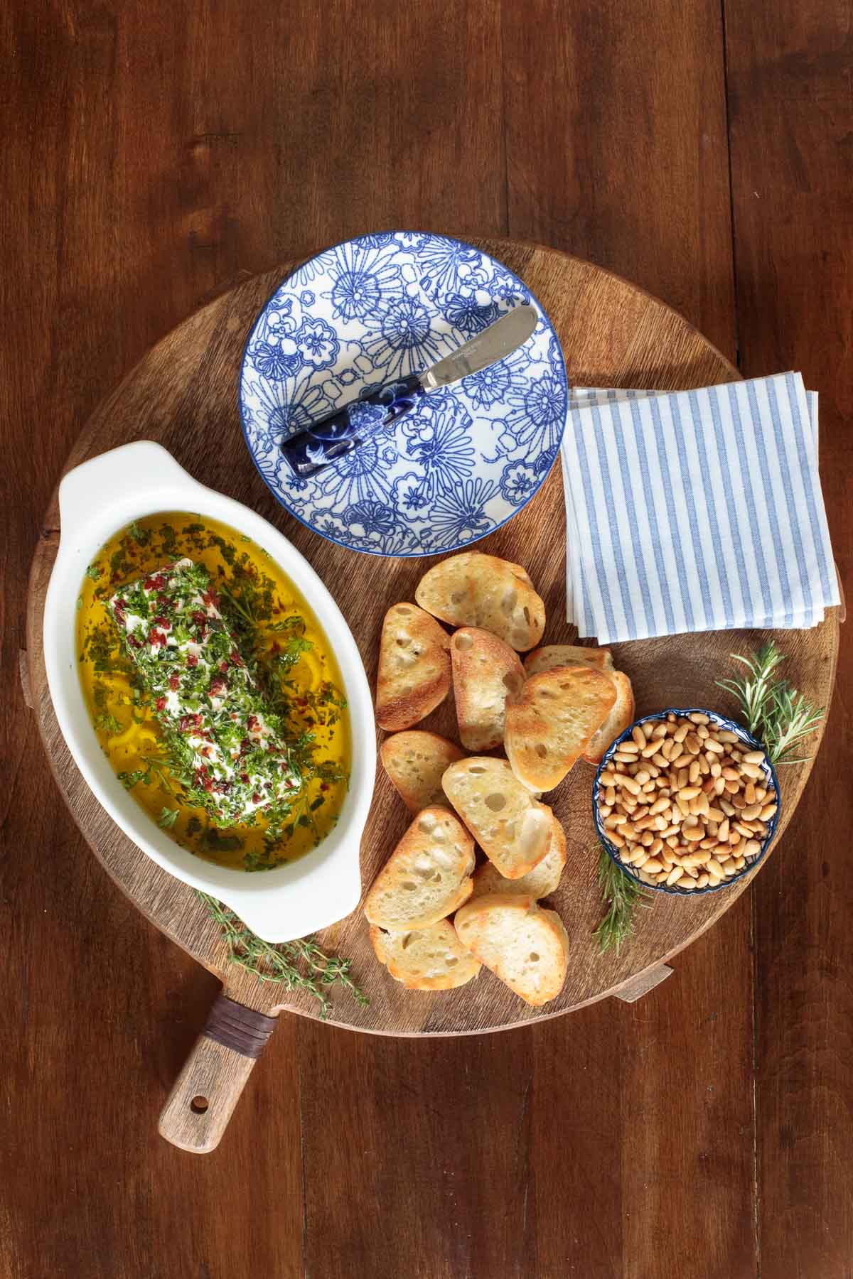 Overhead photo of an appetizer platter featuring Herb Marinated Goat Cheese, toasted french bread and pine nuts.