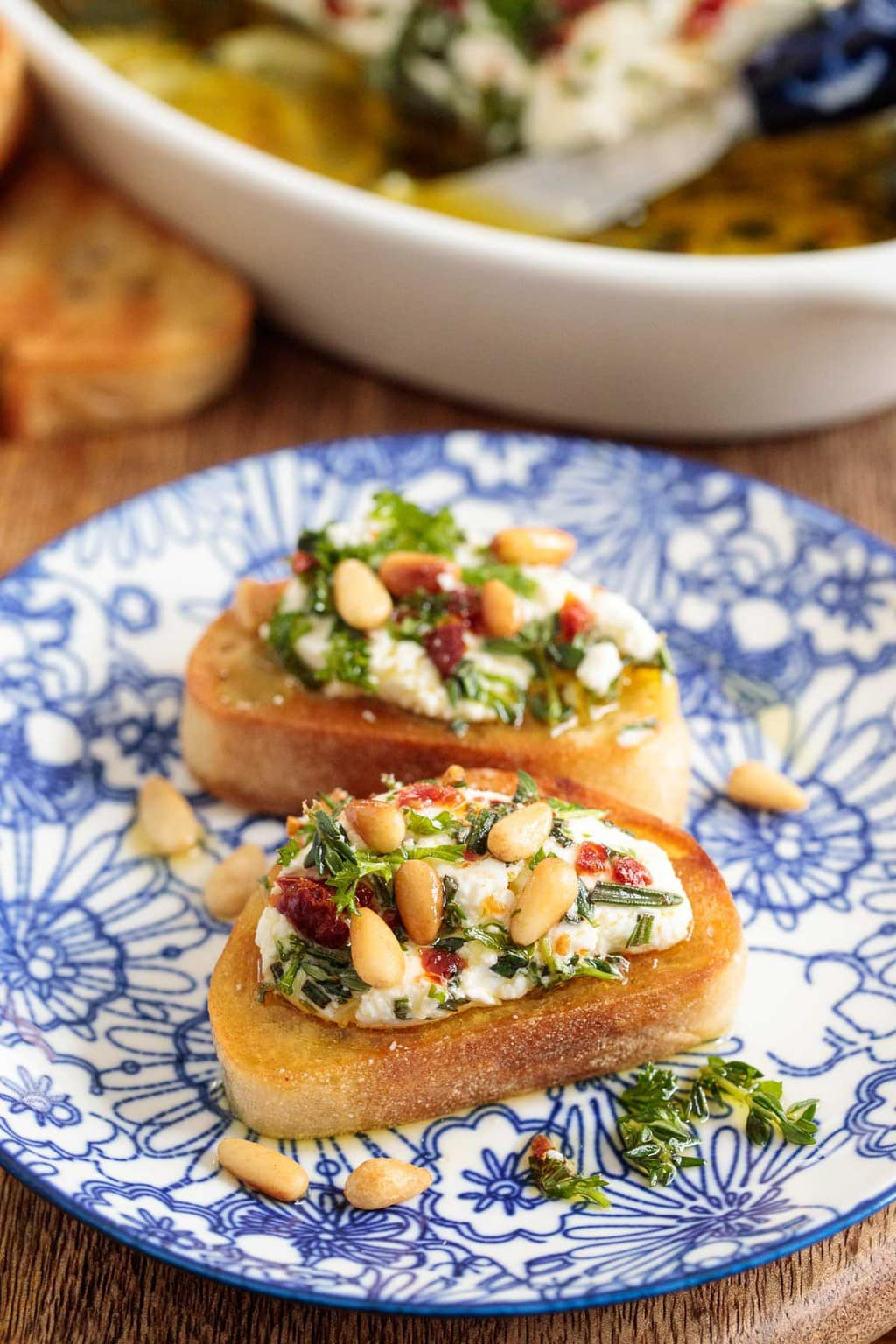 Closeup photo of warm crusty French bread slices spread with Herb Marinated Goat Cheese.