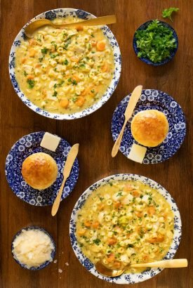 Overhead vertical photo of Creamy Chicken Pasta Soup in blue and white bowls on a wood table.