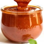 Vertical picture of a glass jar of homemade enchilada sauce
