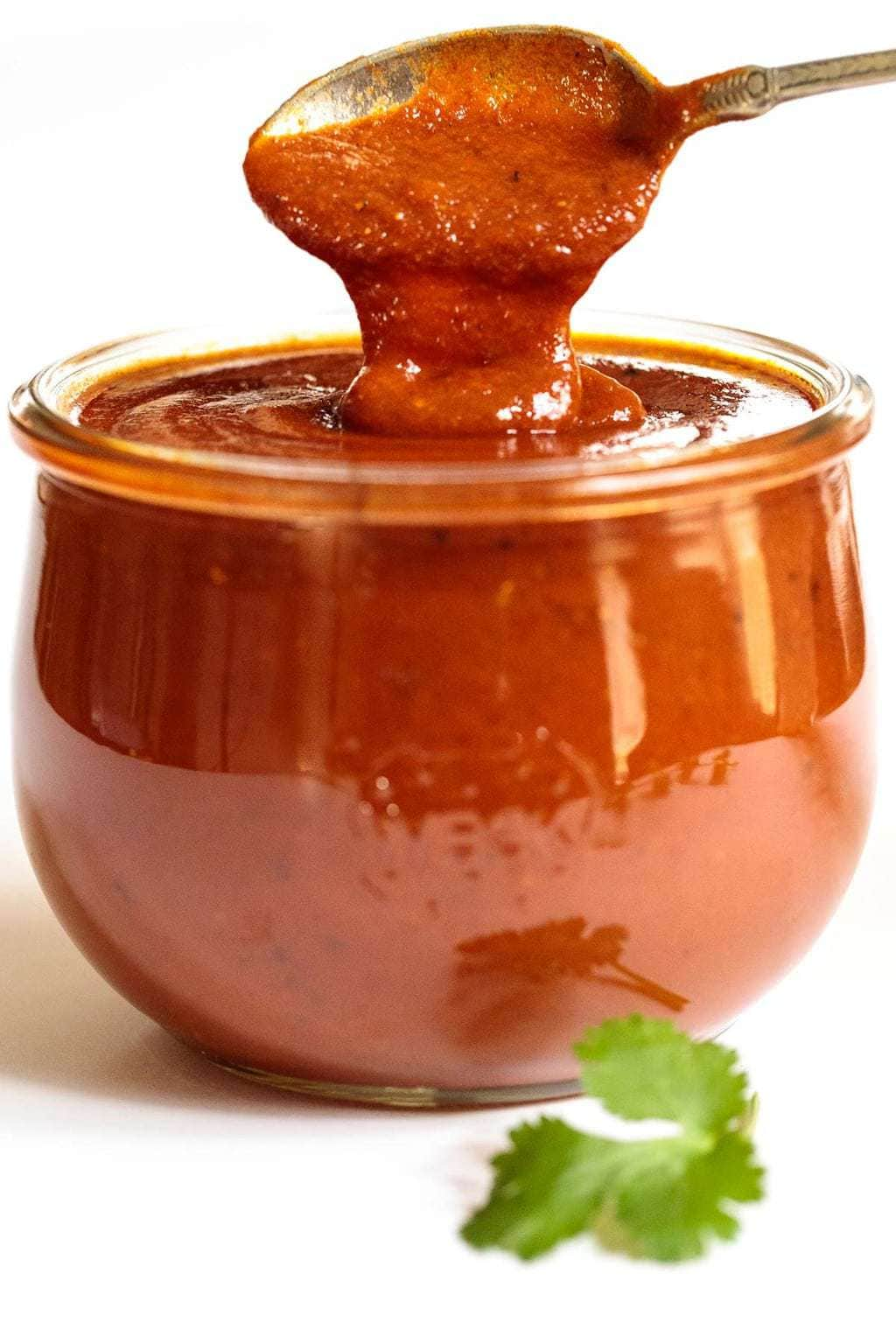 Photo of a Weck jar of 10-Minute Homemade Enchilada Sauce with a spoon dipping into the sauce.