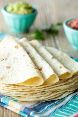 Horizontal photo of a stack of Homemade Flour Tortillas on a colorful kitchen towel.