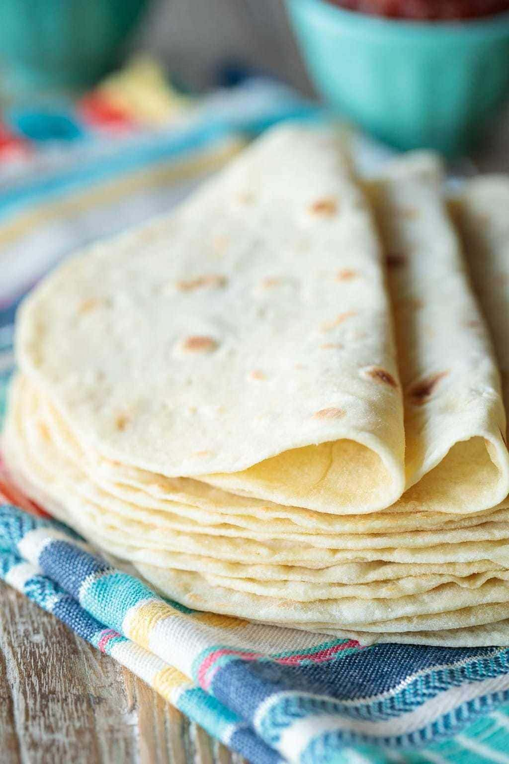 Closeup vertical photo of a stack of Homemade Flour Tortillas on a colorful cloth towel.