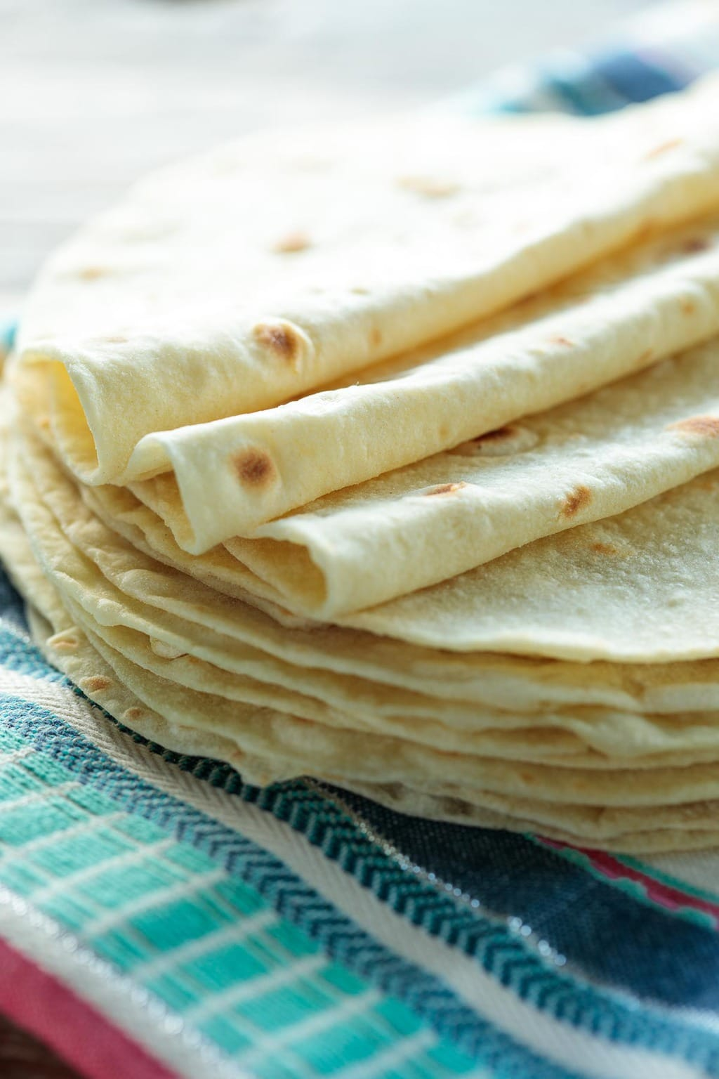 Closeup photo of a stack of Best Ever Homemade Flour Tortillas on a Mexican designed cloth.