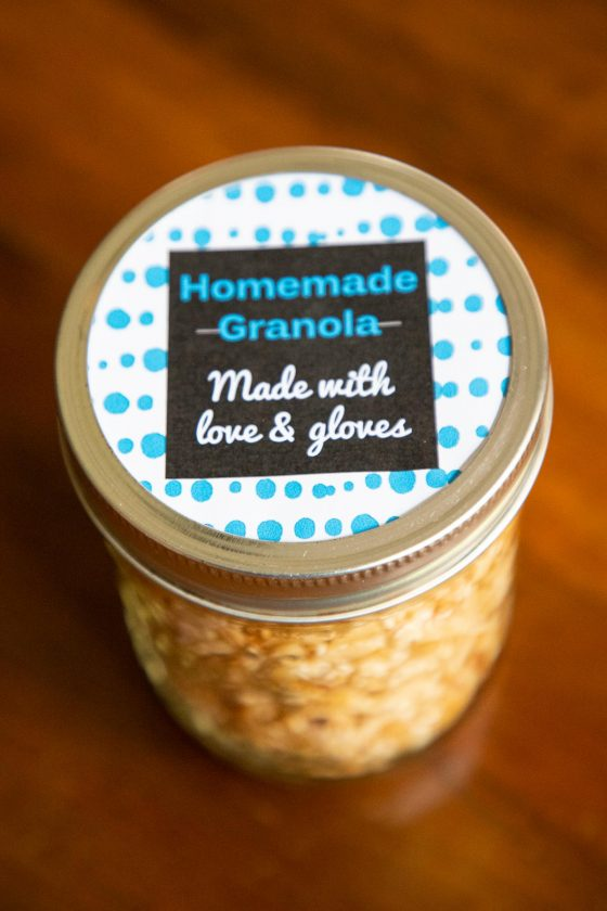 """Vertical photo of a glass jar filled with Homemade Granola with a turquoise and white label saying, """"Homemade Granola - Made with love and gloves""""."""