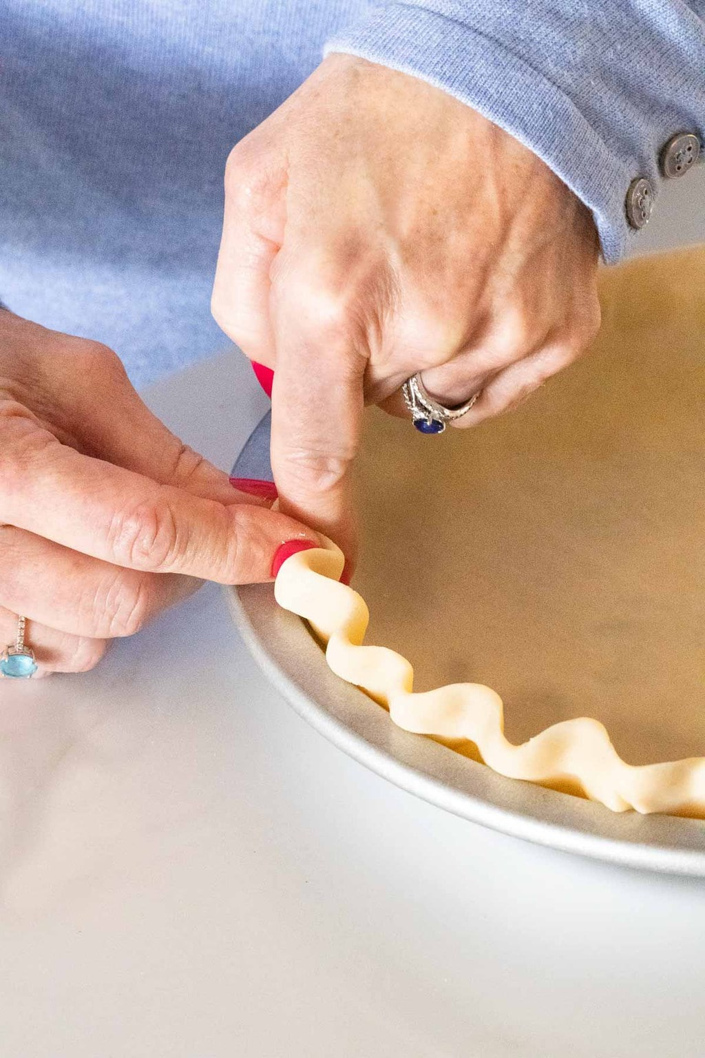 Vertical closeup photo of a person hand crimping the store-bought crust for preparing an Annie's Easy Apple Pie.