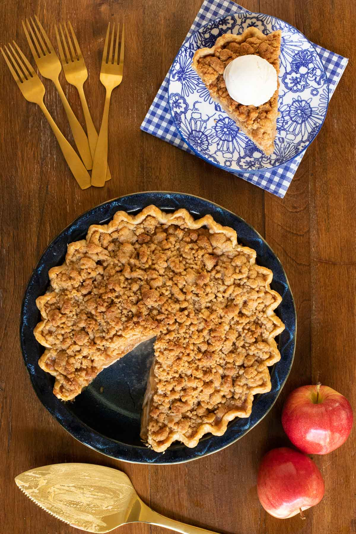 Overhead vertical photo of Annie's Easy Apple Pie on a wood table with a slice of the pie with ice cream on a blue and white patterned plate.
