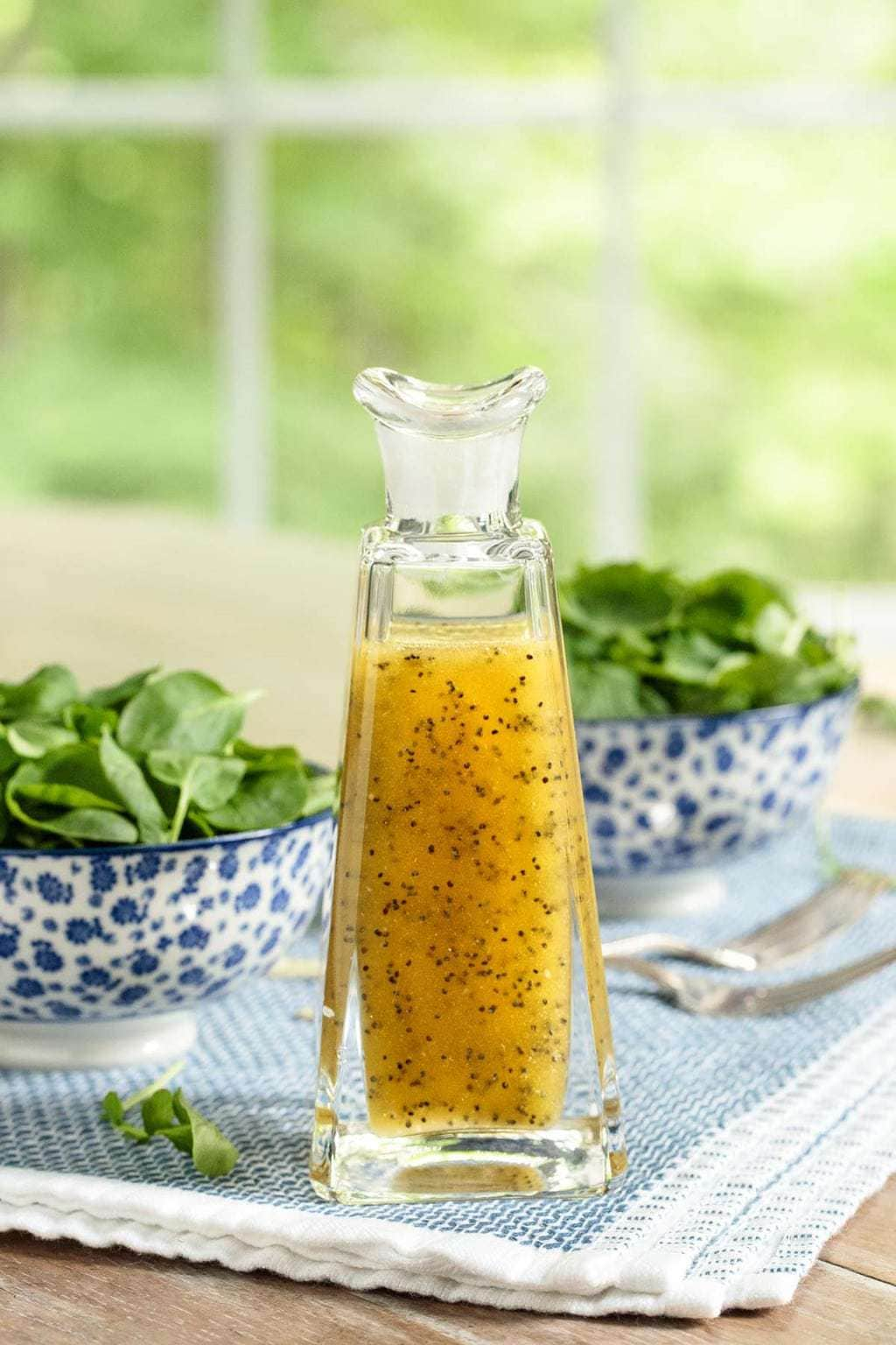 Photo of a glass decanter of Honey-Cider Poppy Seed Dressing a dining room table with bowls of fresh spinach in the background.