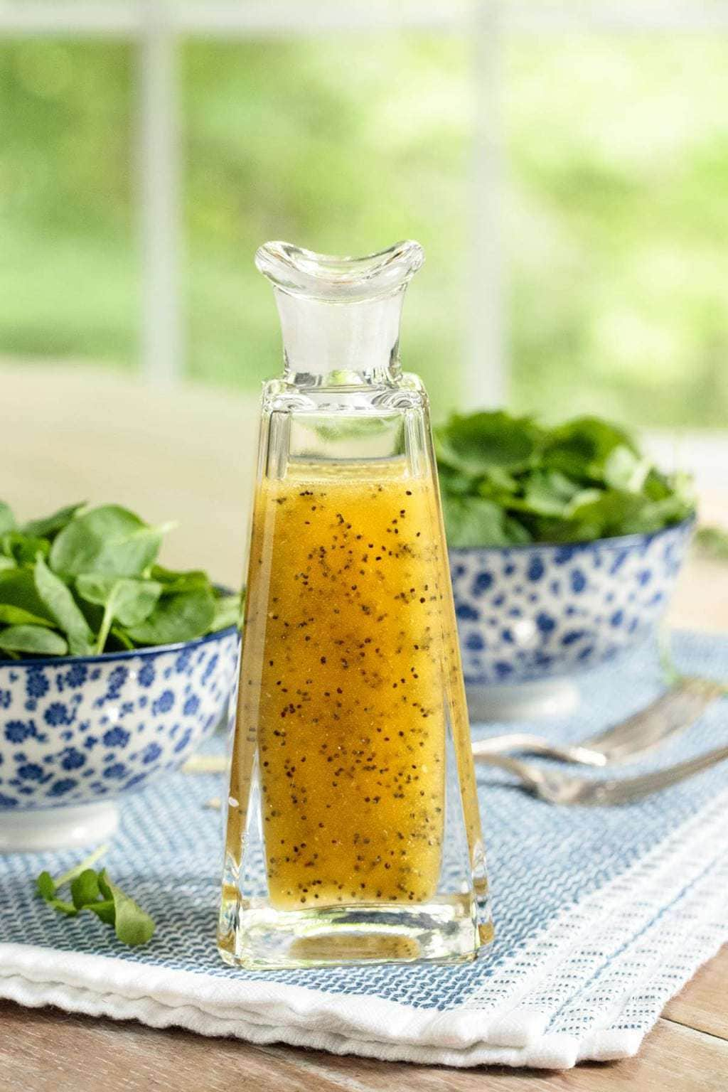 Vertical photo of a glass bottle of Honey-Cider Poppy Seed Dressing on a blue and white patterned cloth with bowls of fresh spinach in the background.