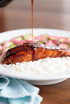 Vertical picture of honey coriander salmon with rice and sauce drizzled over the top in a white bowl