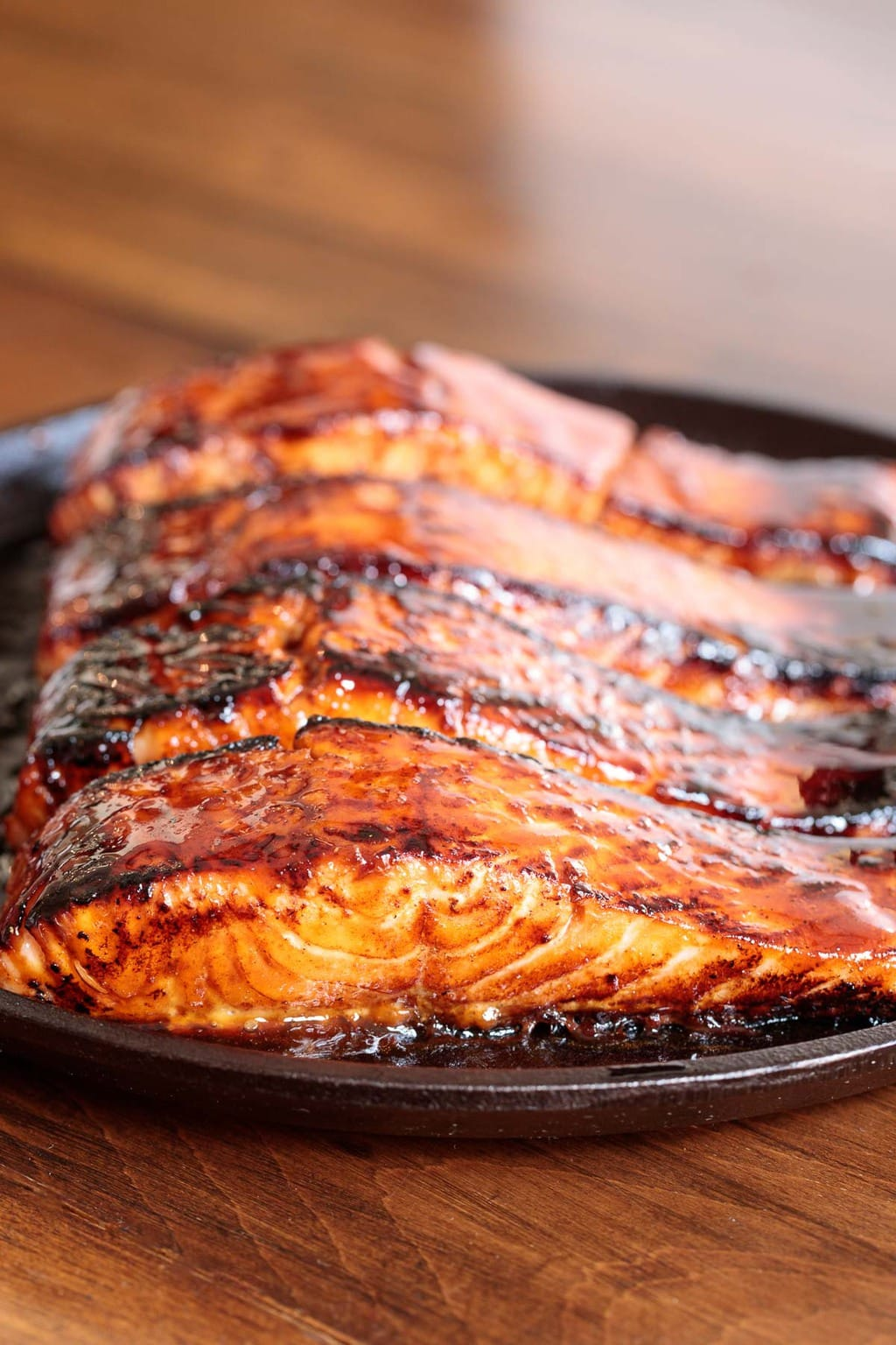 Extreme closeup photo of a piece of Honey Coriander Make-Ahead Salmon in a round iron skillet on a wood table.