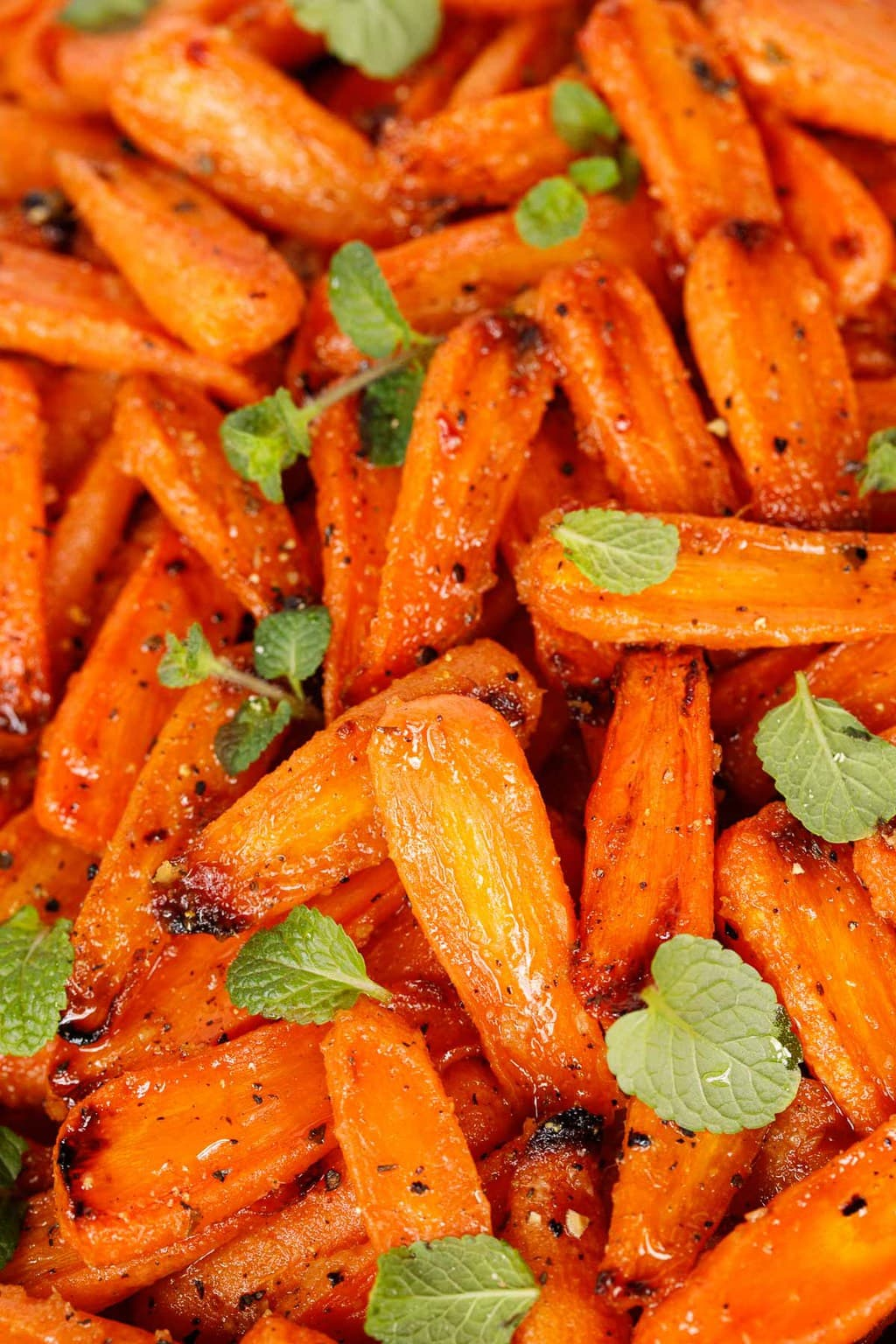 Ultra closeup photo of Honey Ginger Charred Carrots garnished with fresh mint leaves.