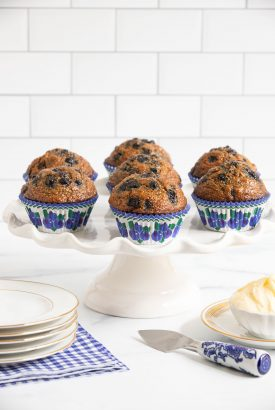 Vertical picture of blueberry bran muffins on a white cake stand
