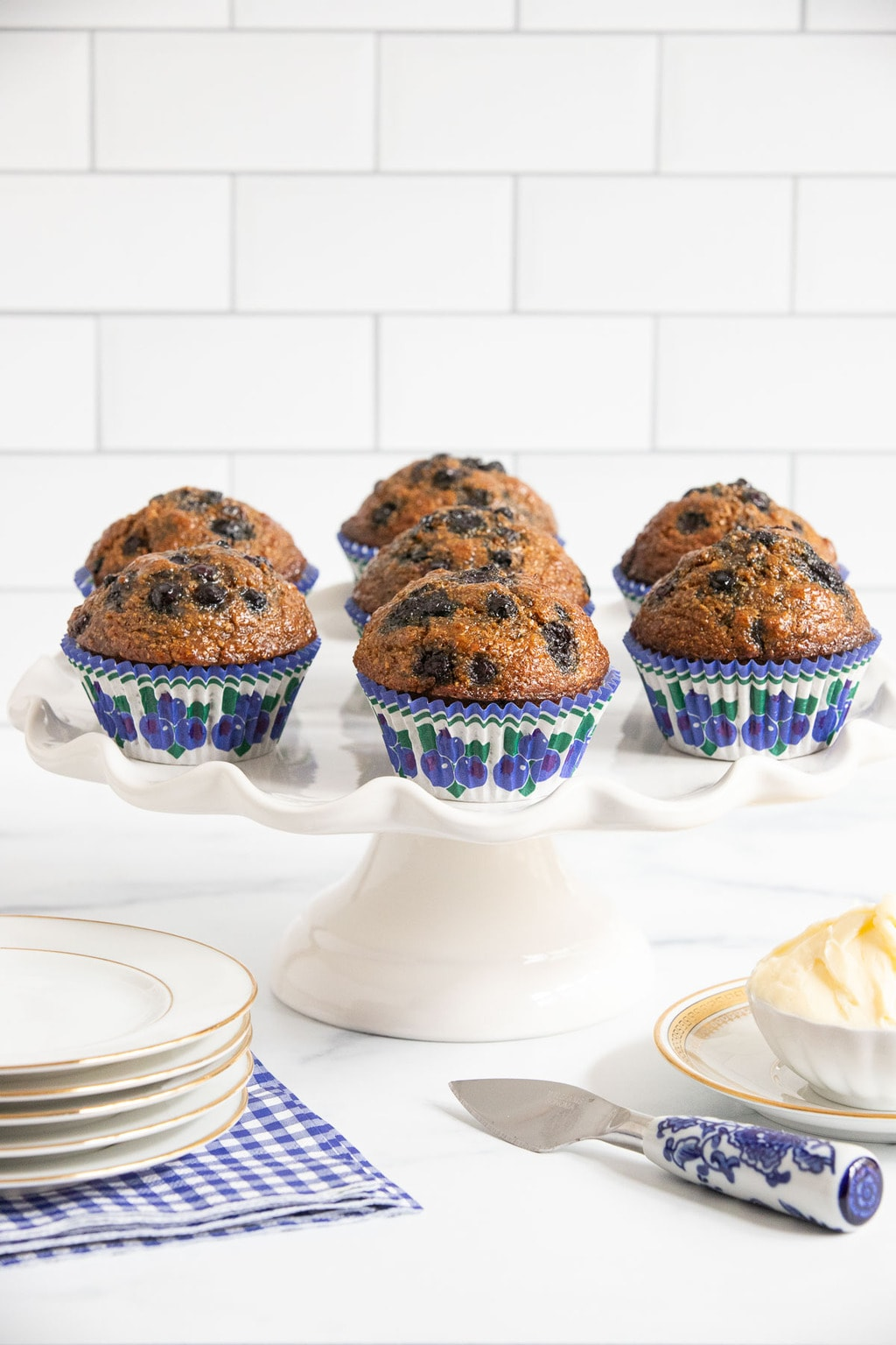 Vertical photo of a batch of Honey-Glazed Blueberry Bran Muffins in green, blue and white cupcake liners on a scalloped pedestal plate.