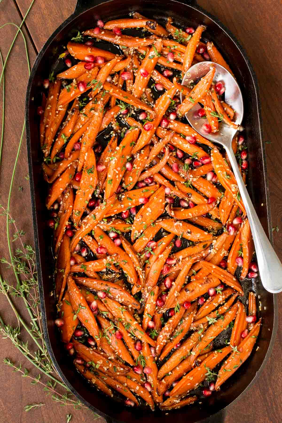 Overhead photo of a cast iron oval dish of Honey Maple Roasted Carrots on a wood table.
