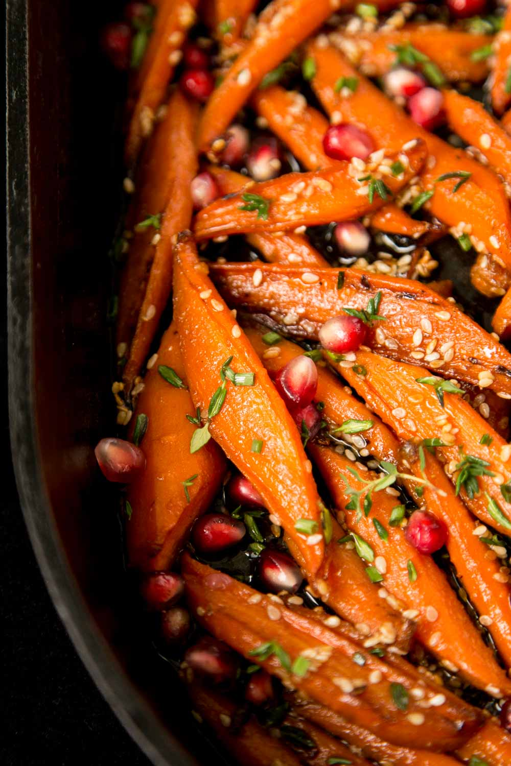 Closeup photo of the side of a cast iron oval pan of Honey Maple Roasted Carrots.