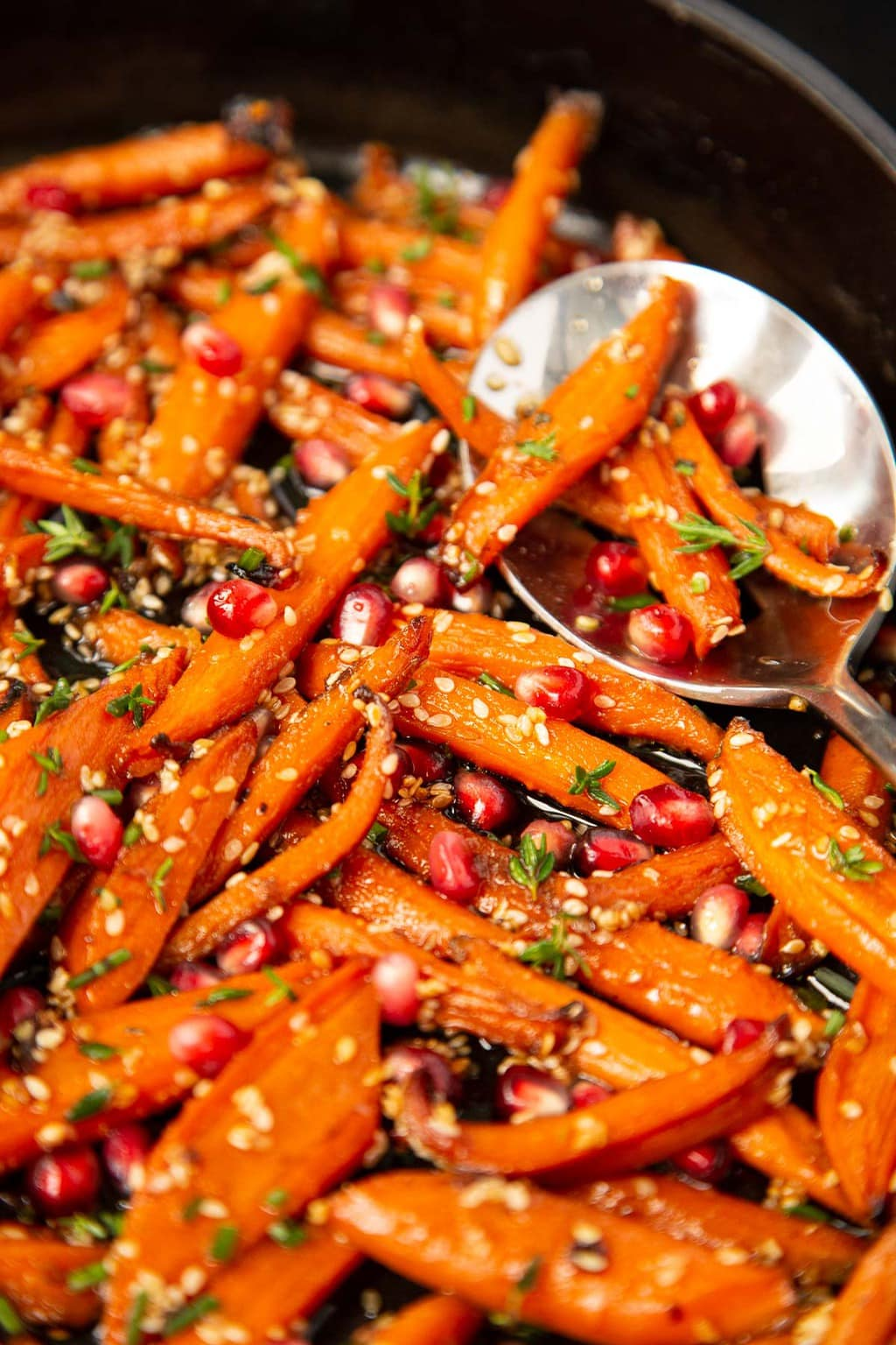 Vertical closeup photo of a cast iron pan filled with Honey Maple Roasted Carrots.