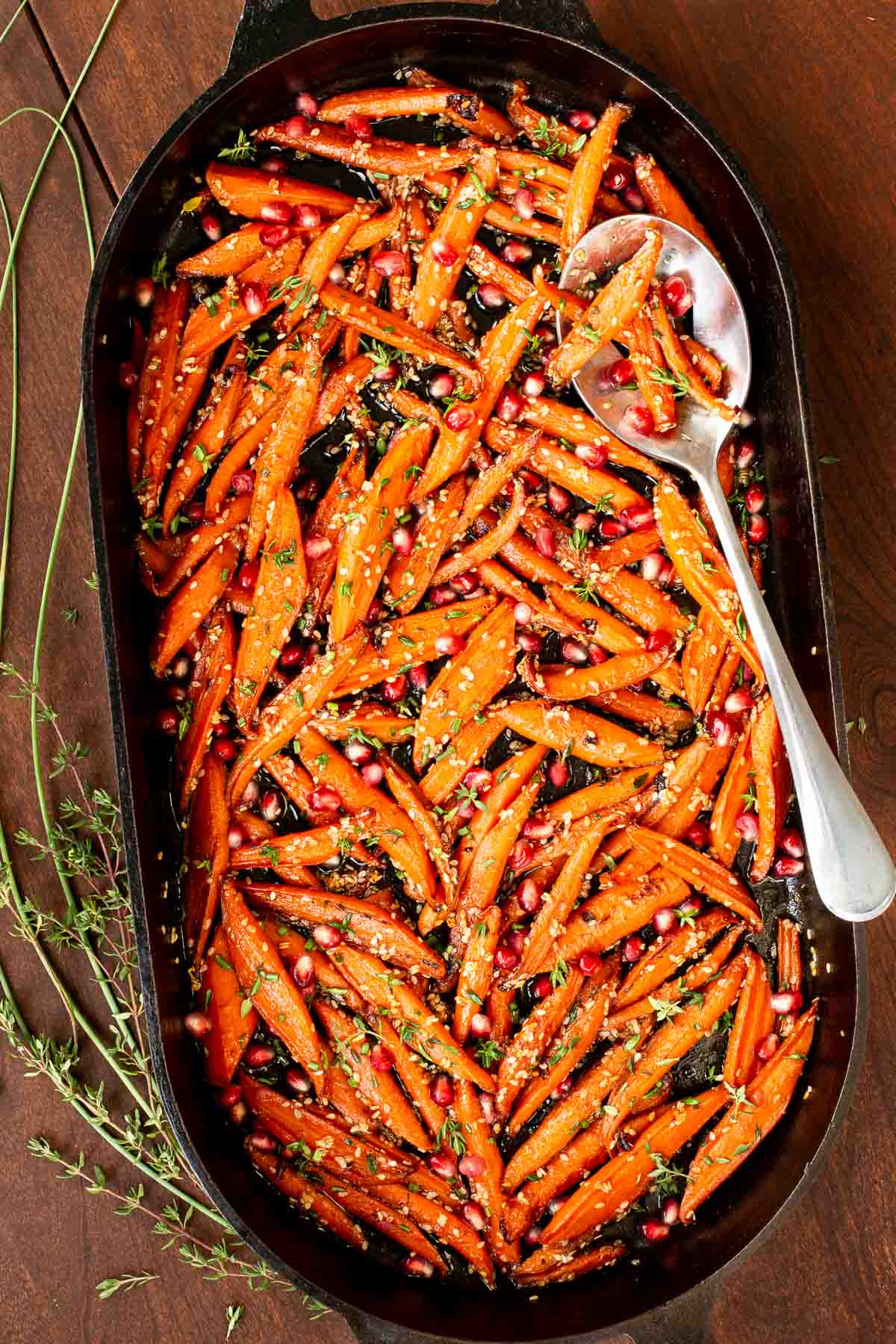 Overhead vertical photo of a cast iron pan filled with Honey Maple Roasted Carrots on a wood table.