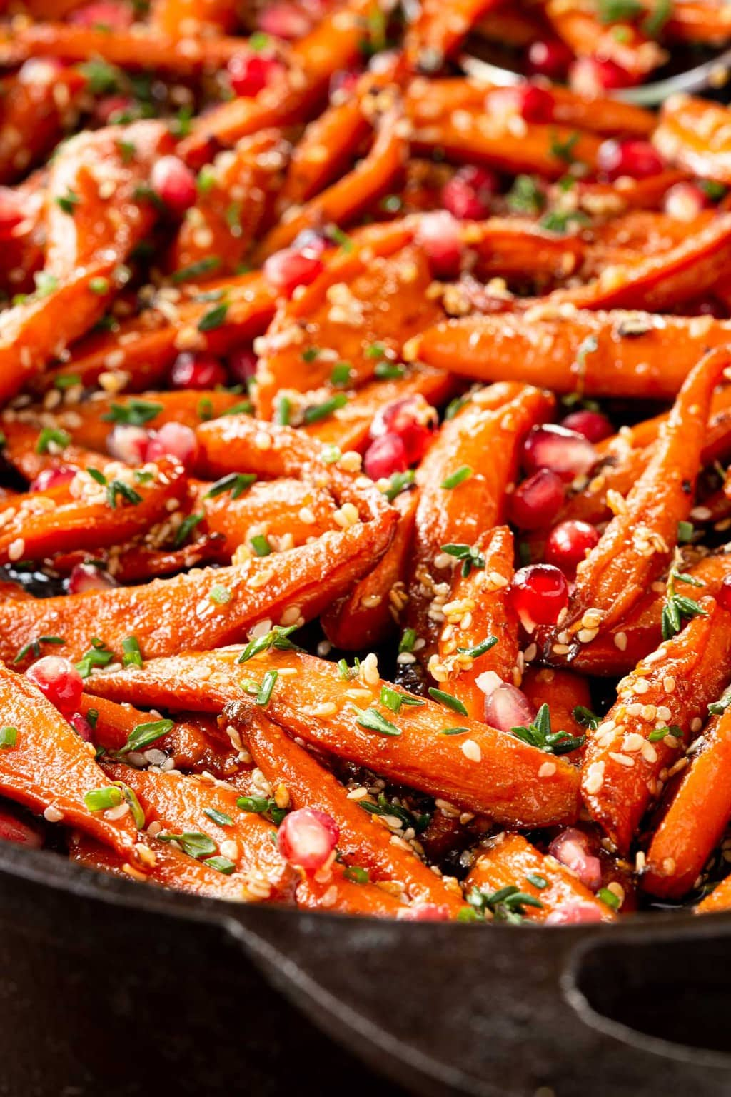 Vertical extreme closeup photo of a cast iron pan filled with Honey Maple Roasted Carrots.