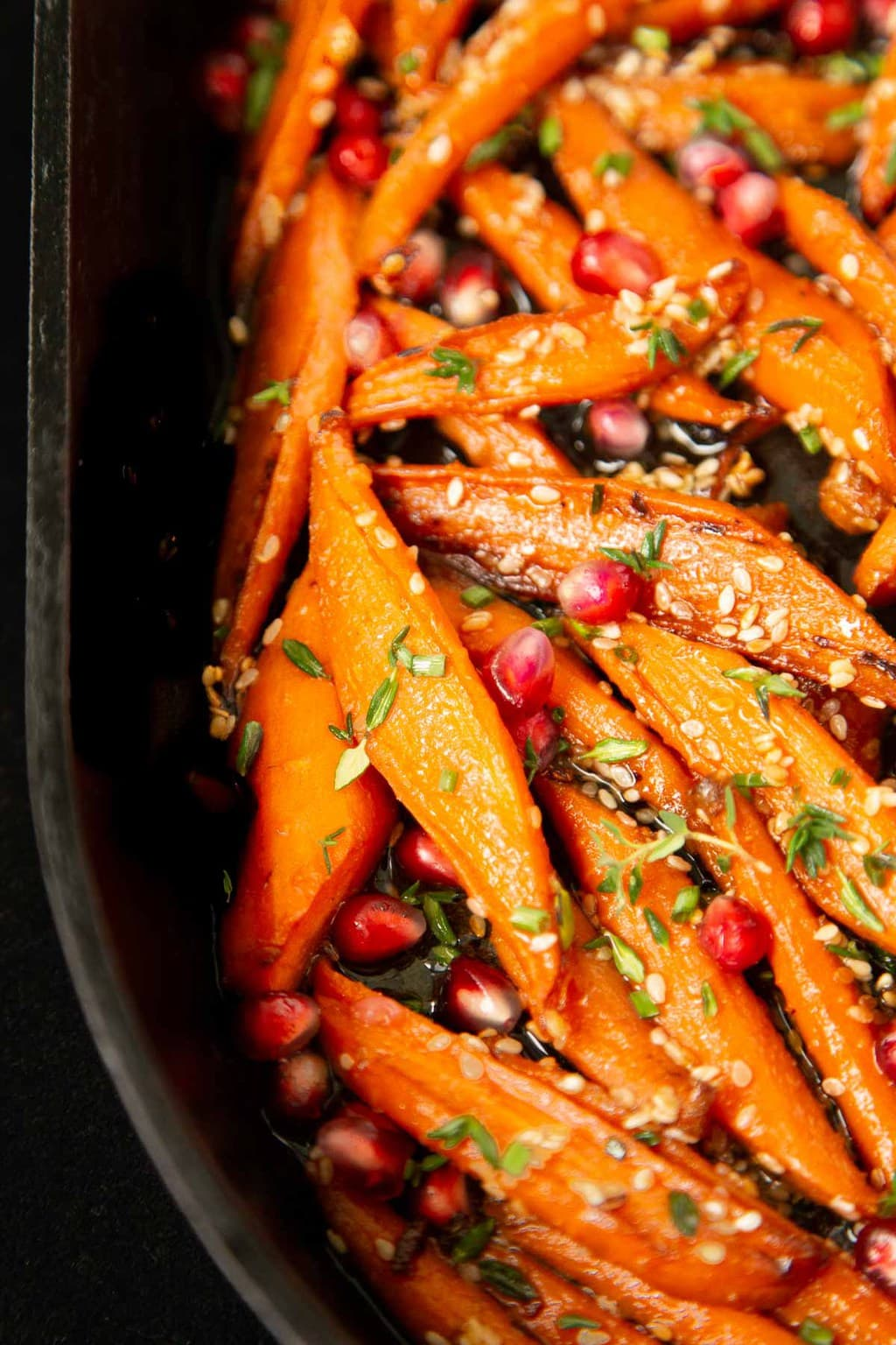 Ultra closeup vertical photo of a cast iron pan filled with Honey Maple Roasted Carrots.