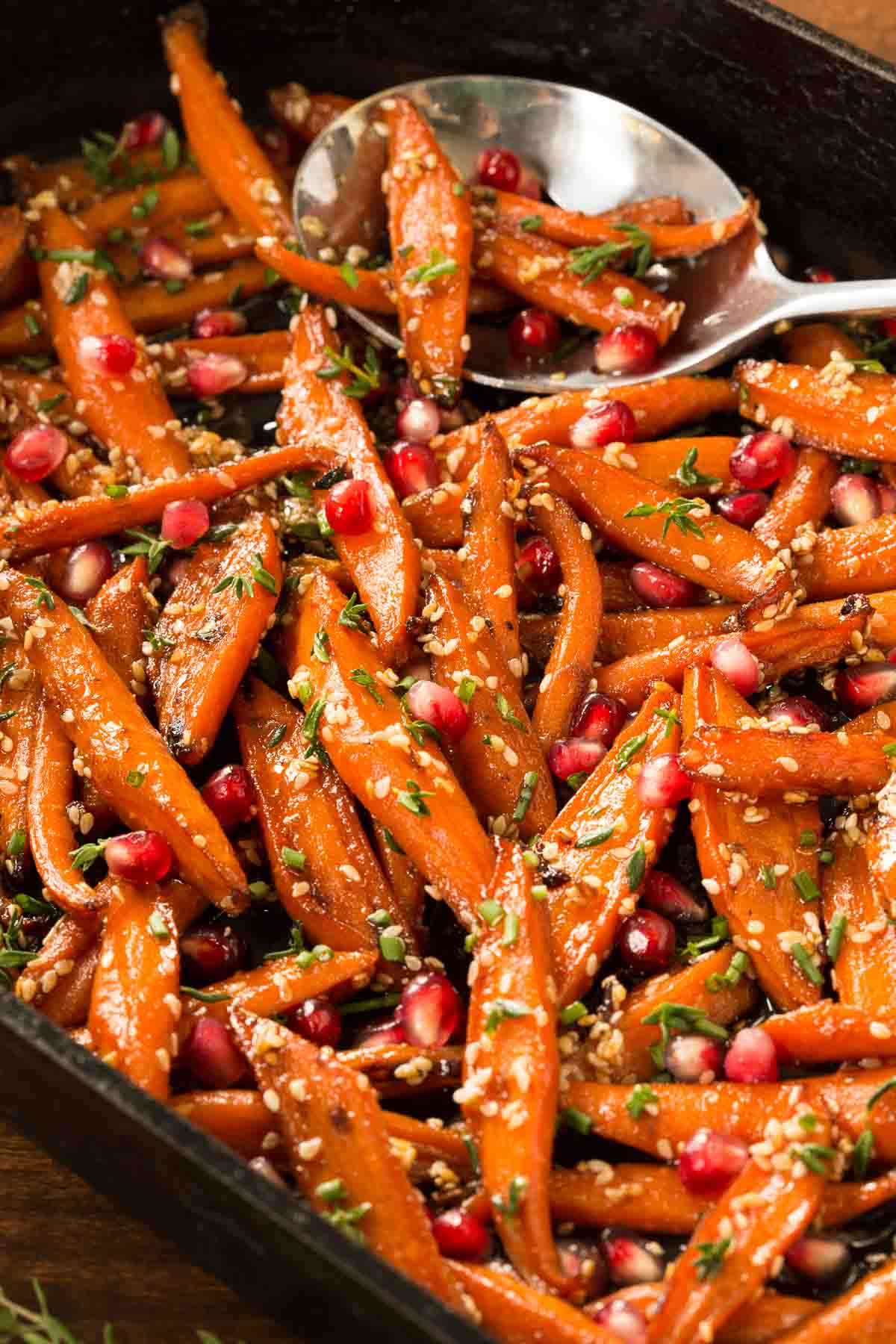 Photo of an oval cast iron pan filled with our Honey Maple Roasted Carrots with a large serving spoon.