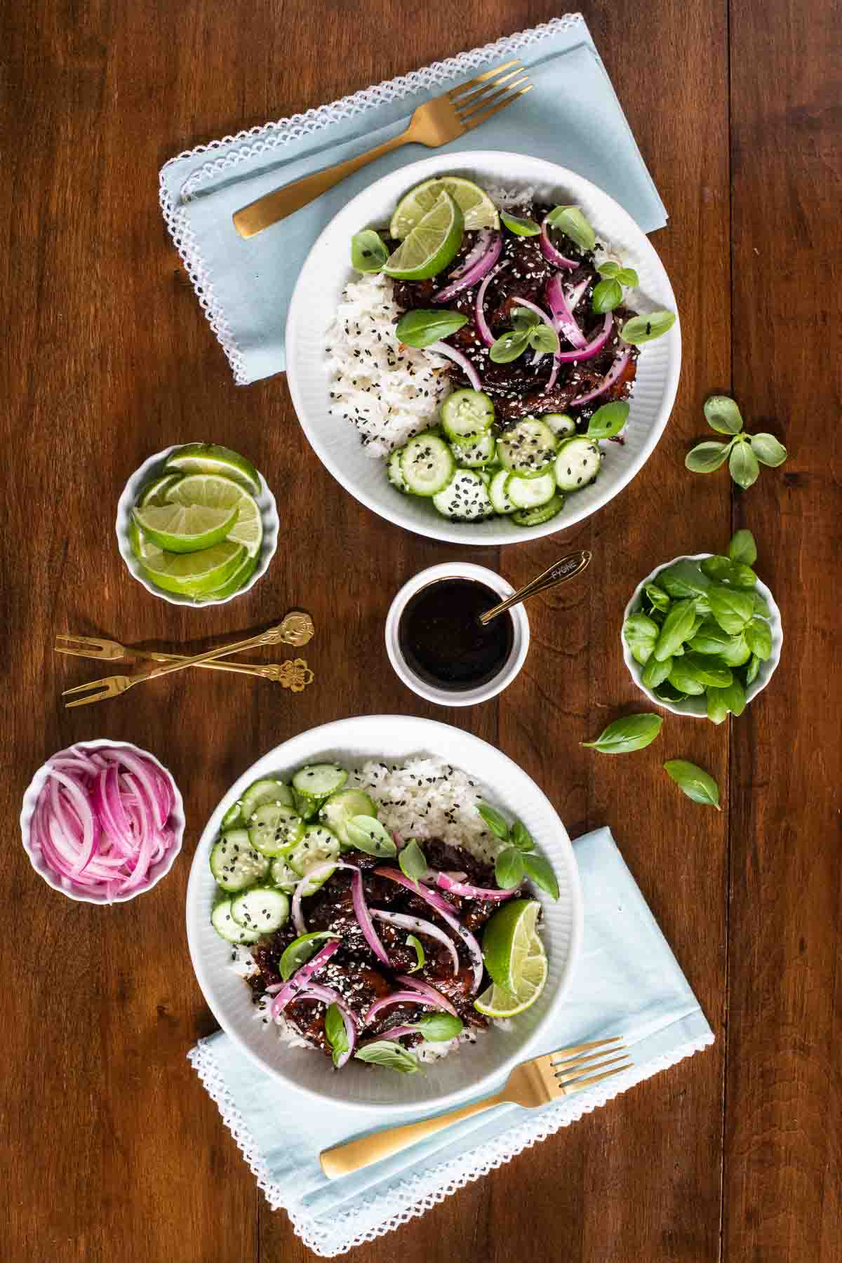 Overhead vertical photo of two rice bowls featuring Honey Soy Braised Pork surrounded by small dishes of lime wedges, pickled red onions and fresh basil.