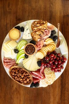 Overhead picture of a cheese board with crackers, fruit, jams, cheese and nuts on a wooden table