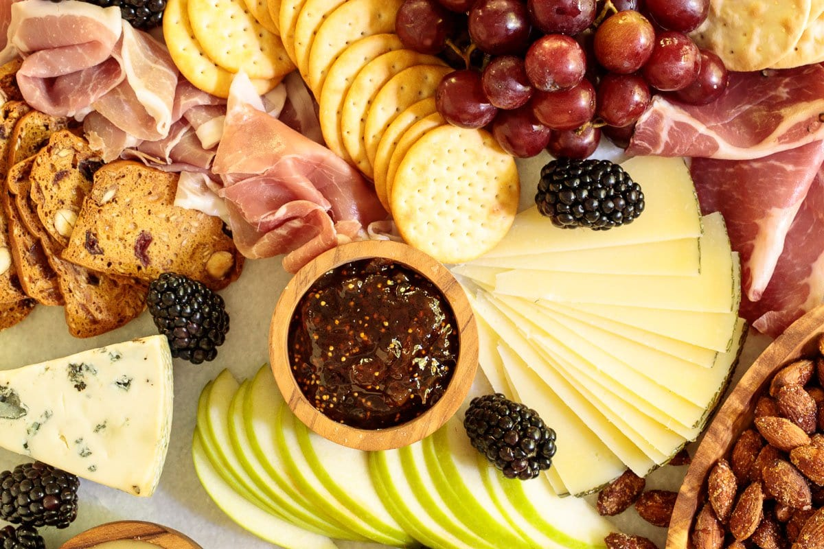 Overhead closeup photo of a cheese board including crackers, meats, hard and soft cheeses, fruit and jam. post.