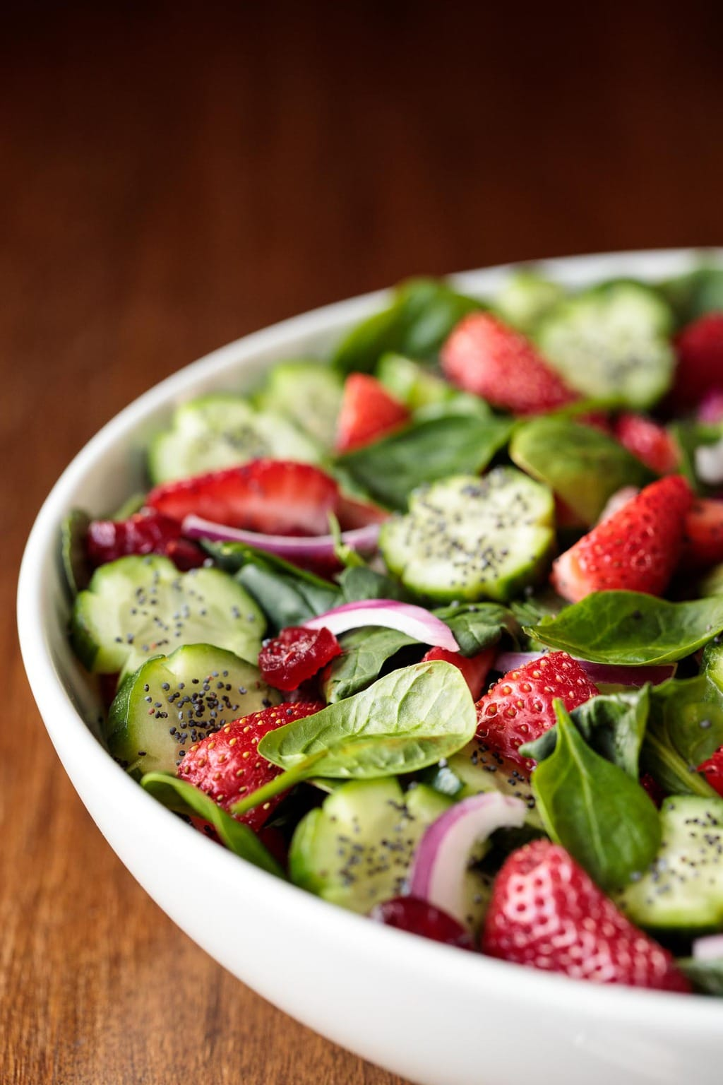 Vertical picture of Strawberry and Cucumber Spinach Salad in a white bowl