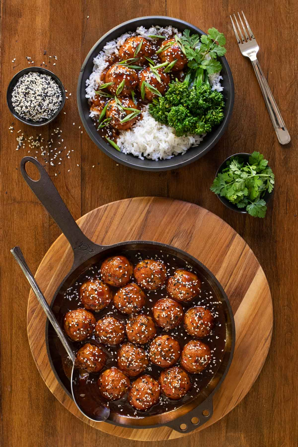 Vertical overhead photo of Huli Huli Chicken Meatballs in a cast iron skillet along side a serving dish with broccoli and rice.