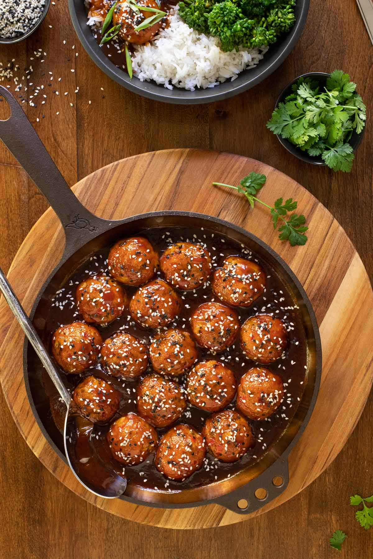 Overhead vertical photo of Huli Huli Chicken Meatballs in a cast iron skillet and also in a serving bowl with rice and broccoli.