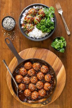 Vertical overhead photo of Huli Huli Chicken Meatballs in a cast iron platter and on a serving bowl with rice and veggies.