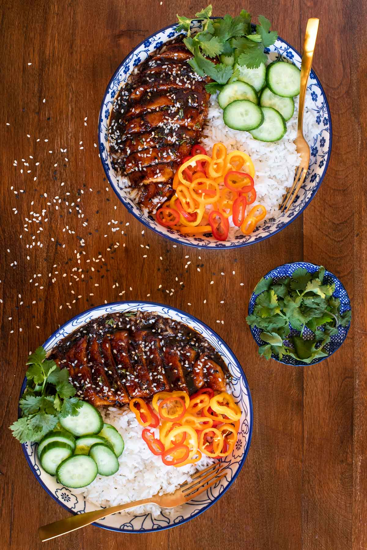 Overhead vertical photo of bowls of Indonesian Sticky Ginger Chicken Breasts with rice, cucumbers, colorful peppers and fresh cilantro.
